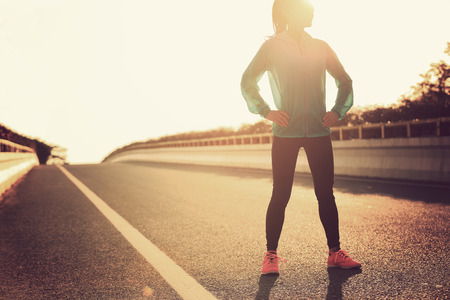 hip: fitness young woman runner standing with her hands on hips on sunrise road