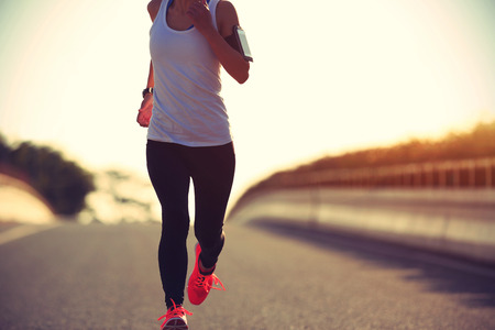 people listening: young fitness woman runner running on sunrise road Stock Photo