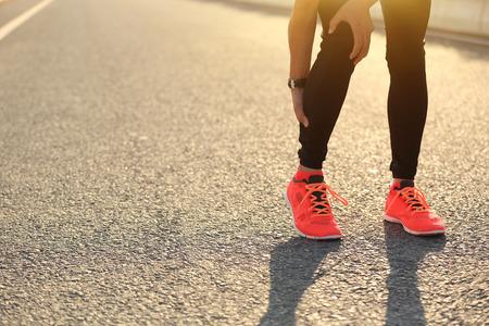 femme coureur tenir sa jambe blessée sur la route