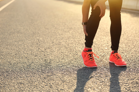 muscle spasm: woman runner hold her injured leg on road