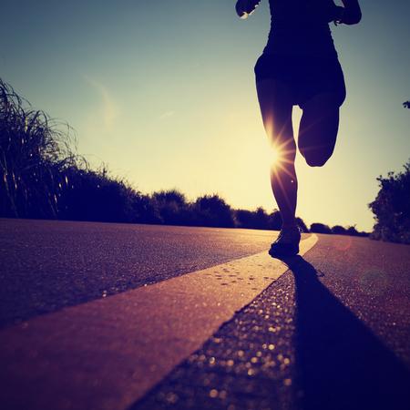 jonge fitness vrouw running op zonsopgang kustweg