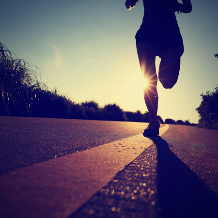 atleta corriendo: joven mujer de fitness running en carretera de la costa del amanecer