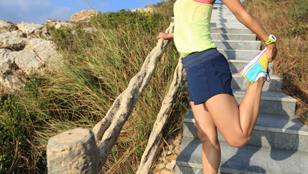 warm up: young fitness woman trail runner warm up on mountain stairs Stock Photo