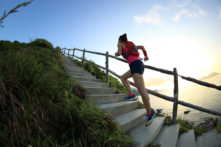 challenge: young fitness woman trail runner on seaside mountain stairs