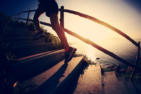 young fitness woman trail runner on seaside mountain stairs Stock Photo