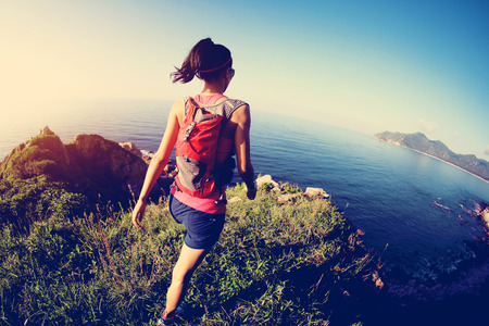 country girls: young fitness woman trail runner on sunrise seaside trail Stock Photo