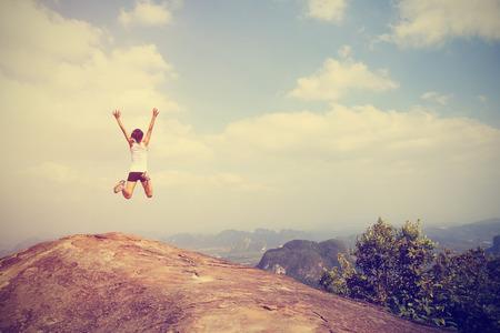 산 꼭대기 바위에 점프 자유 젊은 아시아 여자 스톡 콘텐츠