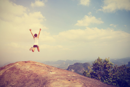 freedom young asian woman jumping on mountain peak rock
