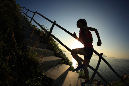 steps to success: young fitness woman trail runner running up on mountain stairs