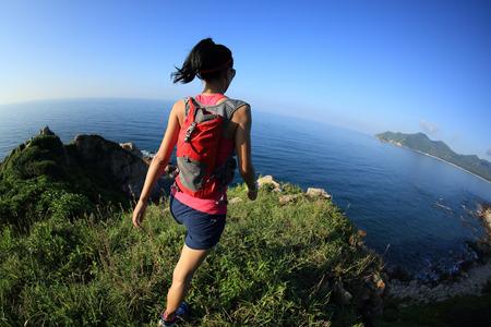 Młoda kobieta fitness szlak runner przy nadmorskiej górskim szlaku