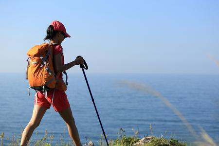 seaside: young woman backpacker walking on seaside mountain trail