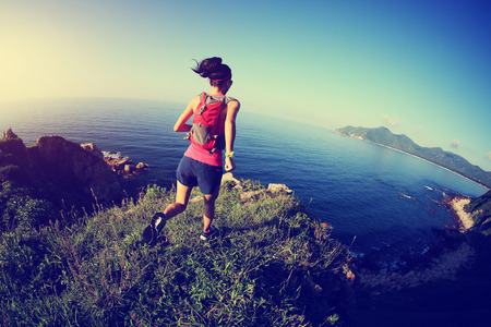 seaside: young fitness woman running on seaside mountain trail Stock Photo