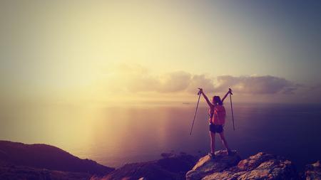 seaside: cheering young woman backpacker at sunrise seaside mountain peak