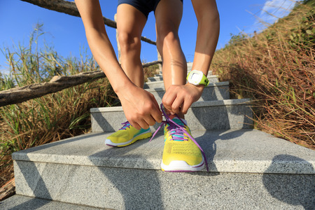 cross ties: young fitness woman trail runner tying shoelace on mountain stairs