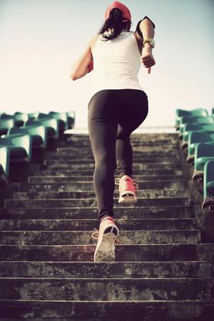 escucha activa: Runner atleta que corre en las escaleras. Aptitud de la mujer trotar entrenamiento concepto de bienestar.