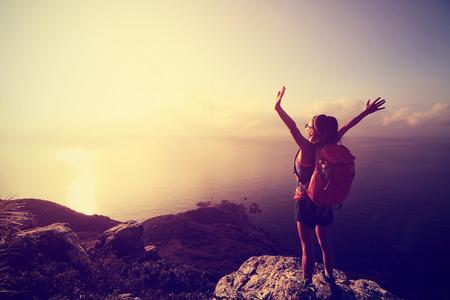 일출 해변 산 피크에서 젊은 여자가 배낭을 응원