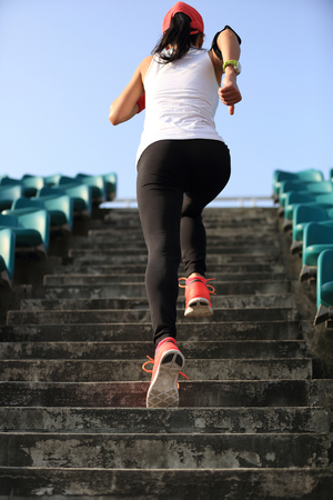 armband: Runner athlete running on stairs. woman fitness jogging workout wellness concept.