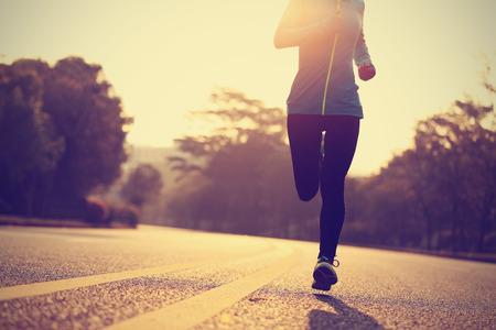jonge fitness vrouw runner atleet loopt op de weg Stockfoto