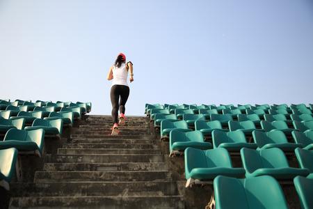 subir escaleras: Runner atleta que corre en las escaleras. Aptitud de la mujer trotar entrenamiento concepto de bienestar.