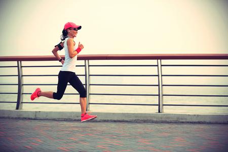 escuchando musica: Joven corredor de la mujer corriente en la carretera costera Foto de archivo