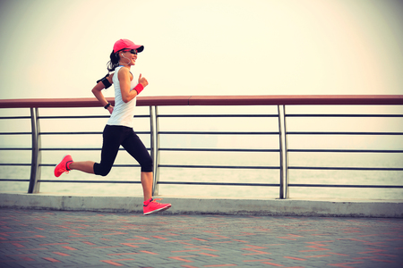 active listening: young fitness woman runner running on seaside road
