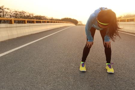 coureur: fatigué femme coureur prendre un repos après avoir couru dur sur la route de la ville Banque d'images