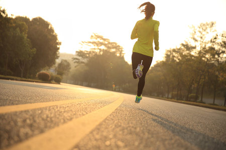 city of sunrise: young fitness woman runner athlete running on sunrise road