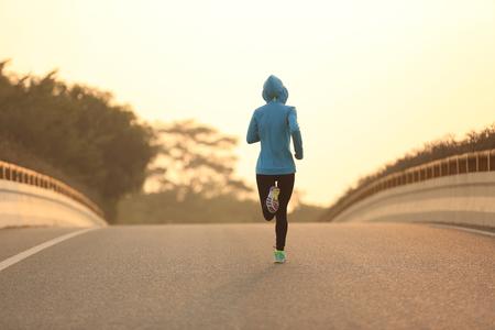 legging: young fitness woman runner athlete running on sunrise road