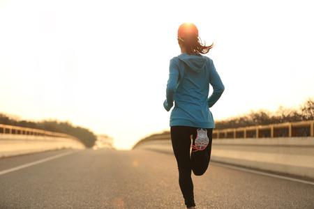 joven atleta corredor mujer corriendo al amanecer carretera de la ciudad