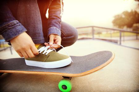 shoelace: skateboarder tying shoelace at skatepark