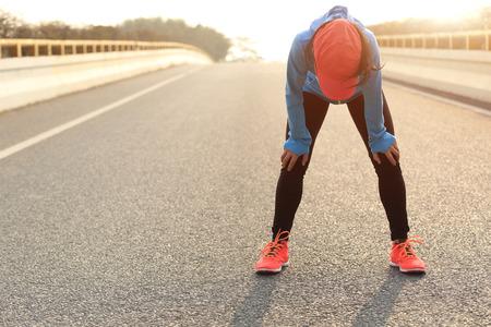 cansancio: Corredor de la mujer cansada de tomar un descanso después de correr duro en el camino de ciudad