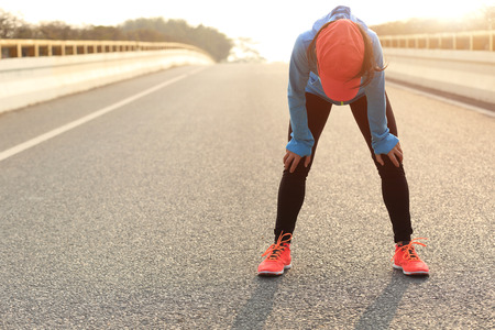 vermoeide vrouw runner nemen van een rust na het lopen hard op stadsweg