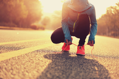 shoelace: young fitness woman runner tying shoelace on road