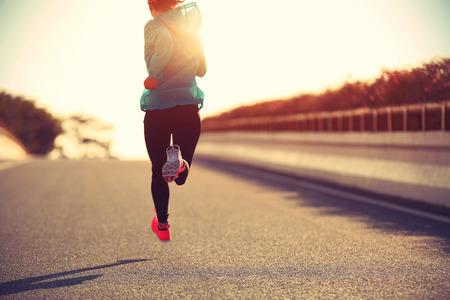 jonge fitness vrouw running op zonsopgang weg