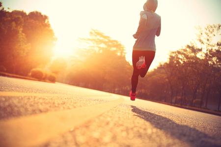 amarillo y negro: Joven corredor de la mujer corriente en la carretera la salida del sol