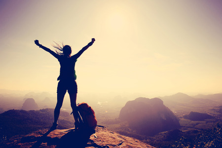 asian success: silhouette of cheering woman hiker open arms at mountain peak