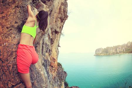 stijger: jonge vrouw bergbeklimmer klimmen bij kust berg rots Stockfoto
