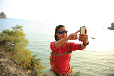 taking photo: young woman hiker use smartphone taking photo on sunset seaside