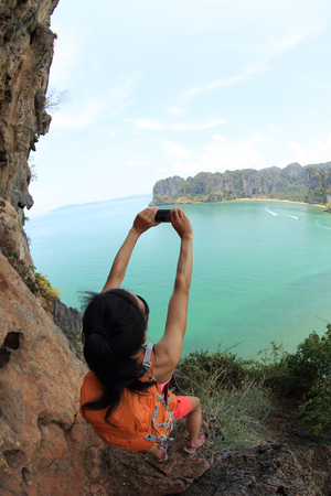 taking photo: young woman hiker use smartphone taking photo on seaside