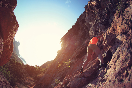 committed: young woman rock climber climbing at seaside mountain cliff Stock Photo