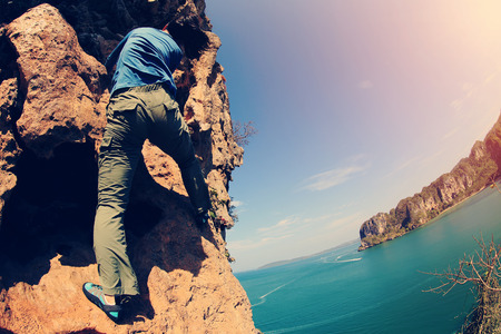 committed: young woman rock climber climbing at seaside mountain rock