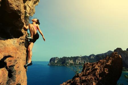 seaside: young woman rock climber climbing at seaside mountain rock