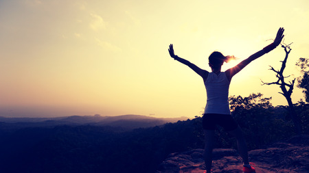 red mountain open space: silhouette of young successful woman open arms on sunset mountain peak Stock Photo