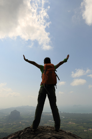 committed: cheering woman hiker open arms at mountain peak Stock Photo