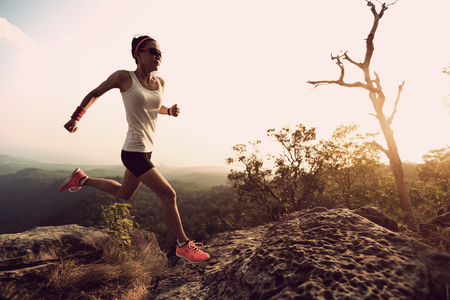 committed: young asian woman runner running on mountain peak