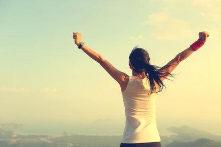 red mountain open space: young successful woman open arms on mountain peak Stock Photo
