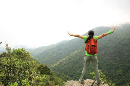 committed: cheering successful woman hiker open arms at mountain peak