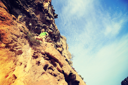 committed: young woman rock climber at seaside mountain cliff