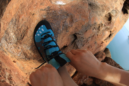 committed: young woman rock climber tying shoelace at mountain rock Stock Photo