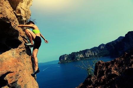 free solo woman rock climber climbing at seaside mountain rock wall Stock Photo